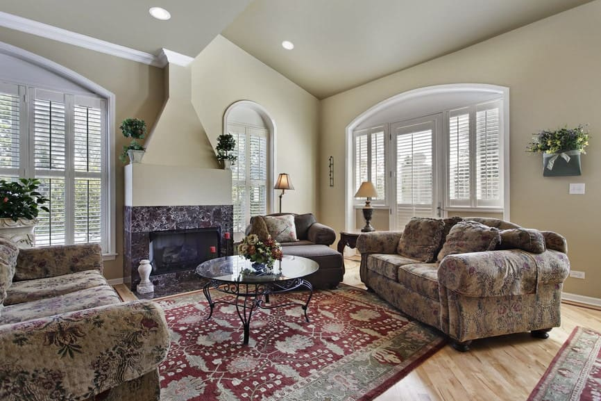 Floral seats surround a glass top coffee table that sits on a red patterned rug over the hardwood flooring. This room has a tiled fireplace and white framed windows bringing natural light in.