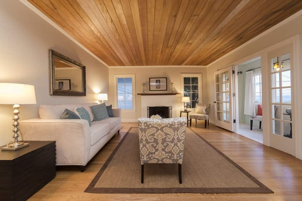 The medium-sized living room showcases a wood plank ceiling and a glazed door that opens to the balcony. It is furnished with patterned chairs and a velvet sofa flanked by dark wood side tables and stylish lamps.
