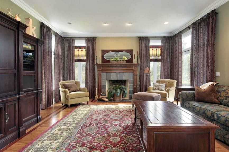Classic living room with a fireplace and mismatched seats paired with a wooden coffee table that complements the hardwood flooring. It includes a red printed rug and patterned draperies covering the full height windows.