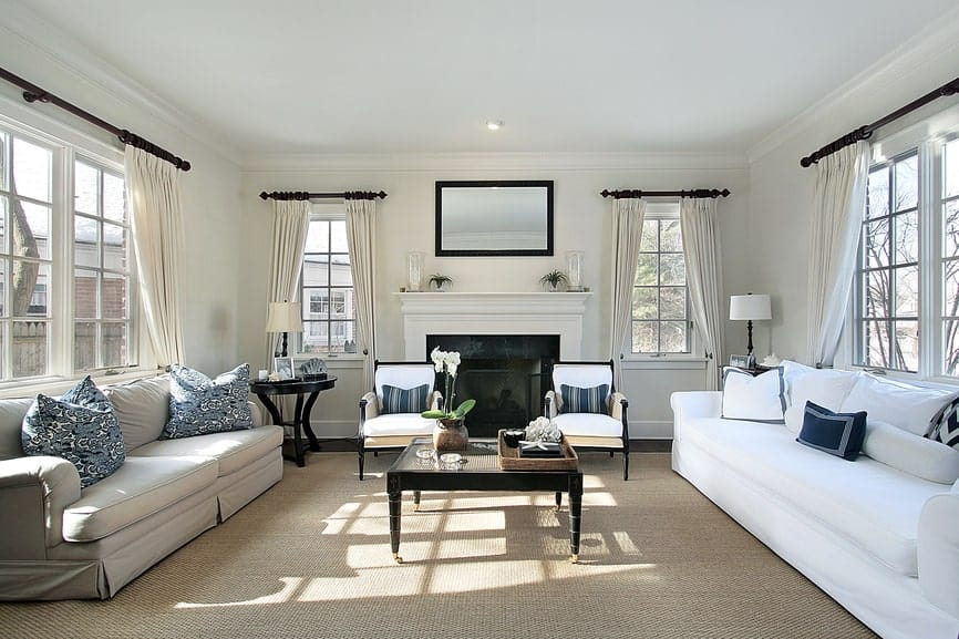 The white living room features a fireplace and sleek seats accented with blue pillows. It includes framed windows and a glass top coffee table that sis on a large woven rug.