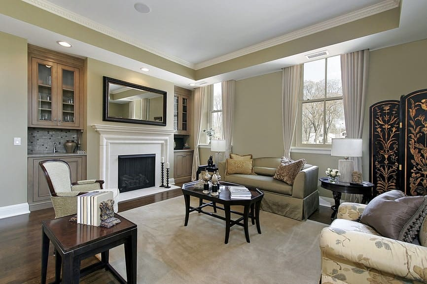 A wooden framed mirror hangs above the white fireplace flanked by built-in cabinets. There are mismatched seats and dark wood coffee tables along with a beige area rug that lays on the hardwood flooring.