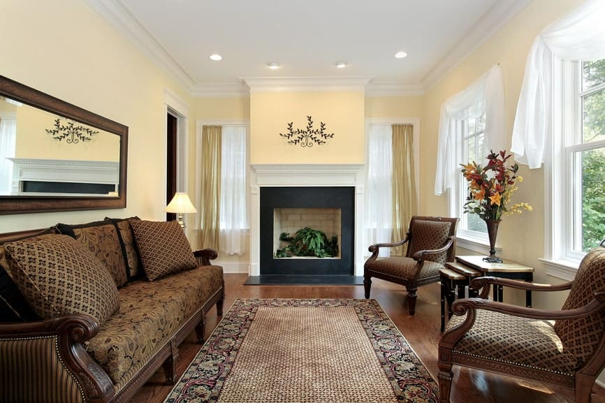 Formal living room with a fireplace and cushioned seats surrounding a bordered area rug that lays on the hardwood flooring. It includes a rectangular mirror and white framed windows dressed in sheer valances.