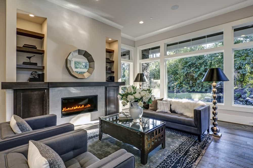 A gorgeous mirror hangs above the fireplace facing the wooden coffee table placed in between a gray tufted sofa and matching armchairs. It is lighted by stylish floor lamps along with natural light that flows in through the glazed windows.