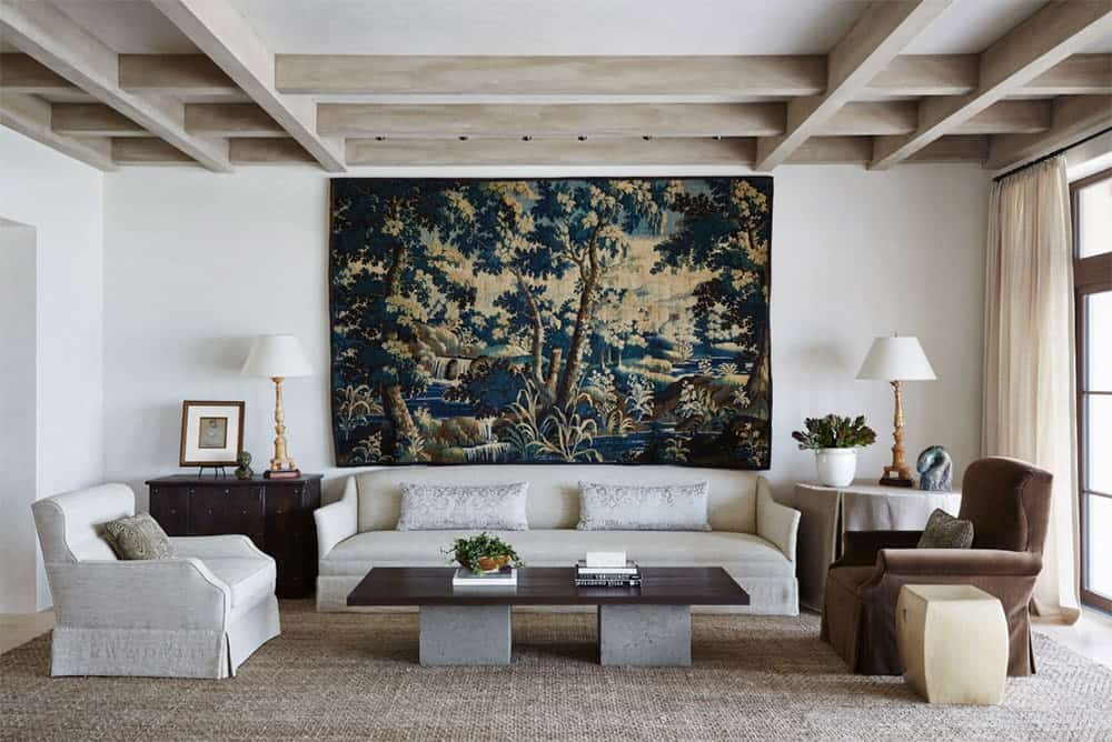 A woodland tapestry sets a gorgeous backdrop to the gray sofa paired with a wood plank coffee table. This room has coffered ceiling and light hardwood flooring topped by a jute area rug.