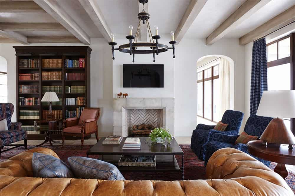 A chesterfield sofa faces the dark wood coffee table and tiled fireplace with a wall mount TV on top. There's a bookshelf on the side accompanied by mismatched chairs and a round side table.