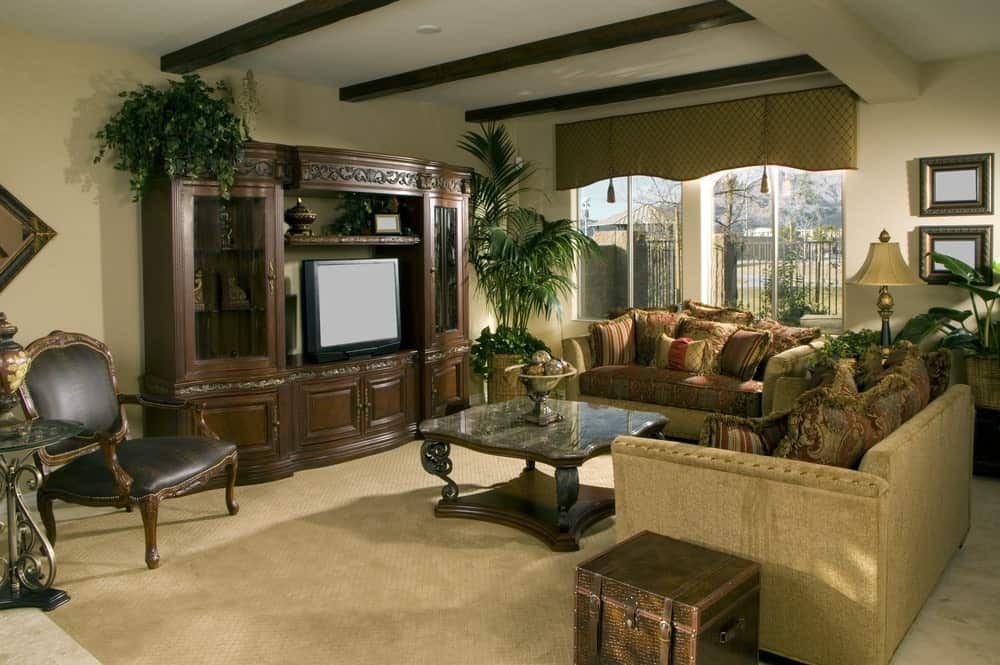 A patterned valance covers the glazed windows overlooking the serene outdoor view. This room has classy seats and coffee table facing the TV placed on the carved wood cabinet.