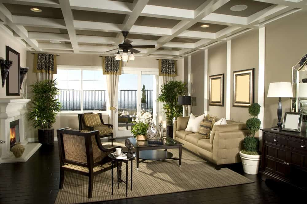 The fresh living room showcases a dark wood coffee table and beige sectional along with cushioned chairs that complement the striped area rug. It has wide plank flooring and coffered ceiling mounted with a fan and recessed lights.