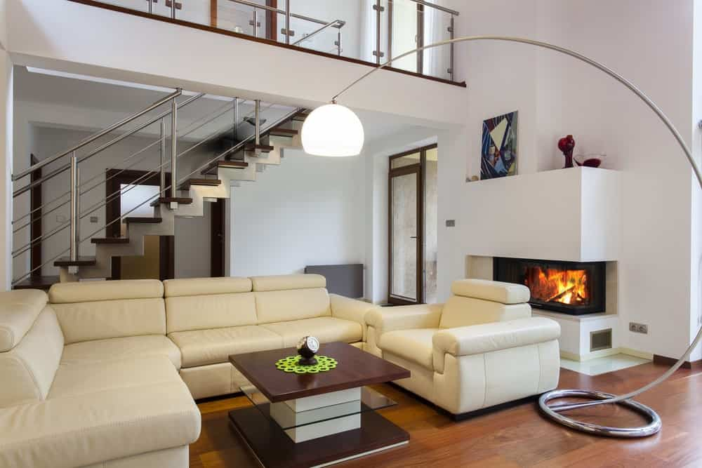 An arched floor lamp illuminates the sleek seats and coffee table over the rich hardwood flooring. There's a fireplace on the side fixed on the white inset wall.