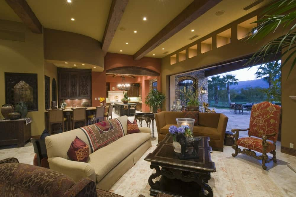 An open living room with mismatched seats and a dark wood coffee table that sits on a floral area rug. It has limestone flooring and a moss green ceiling lined with rustic wood beams.