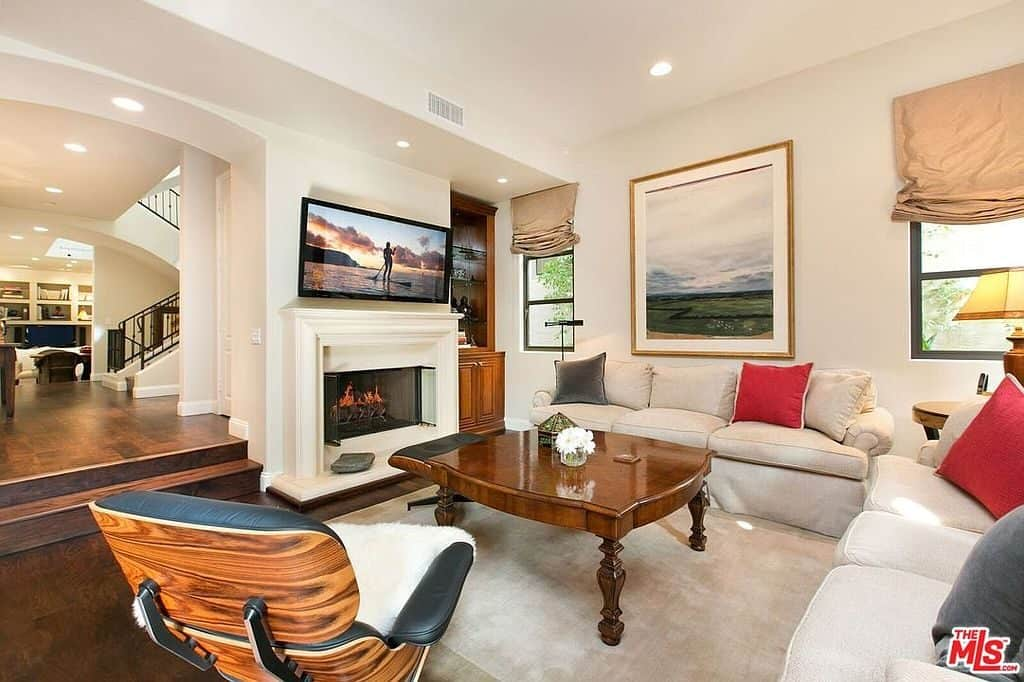 A wall mount TV hangs above the fireplace facing the wooden coffee table surrounded by cozy seats. This living room is decorated with a landscape painting flank by framed windows that are covered in beige roman shades.