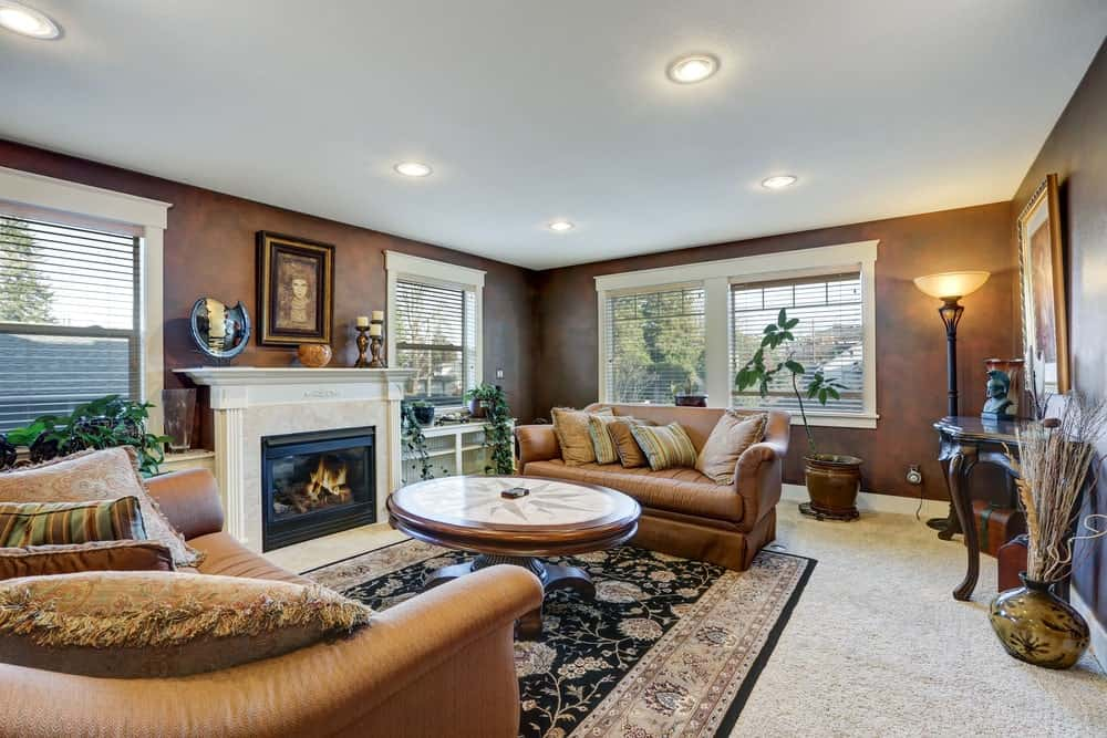 Sophisticated living room decorated with a lovely portrait that hung above the fireplace facing the round coffee table. It has brown sofas and a black floral rug that lays on the carpet flooring.