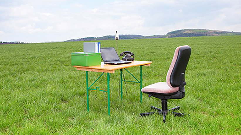 A computer and desk in the middle of a field