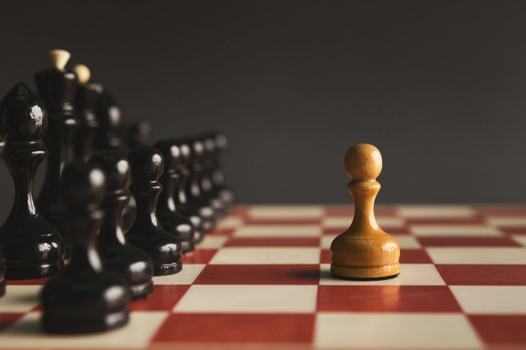 One pawn standing against set of black chess