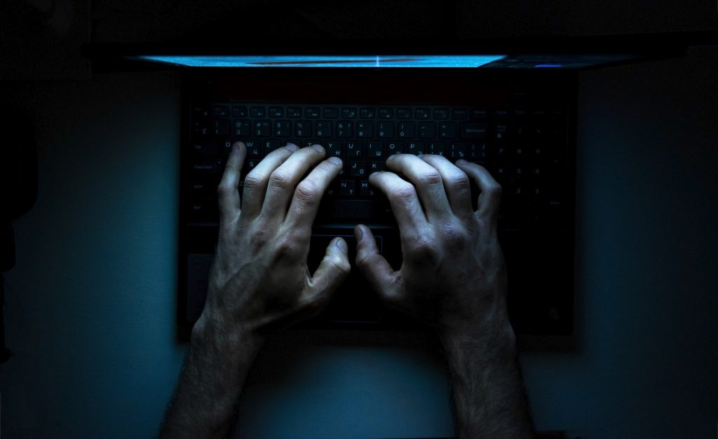 Top view of the hands of a programmer on his laptop