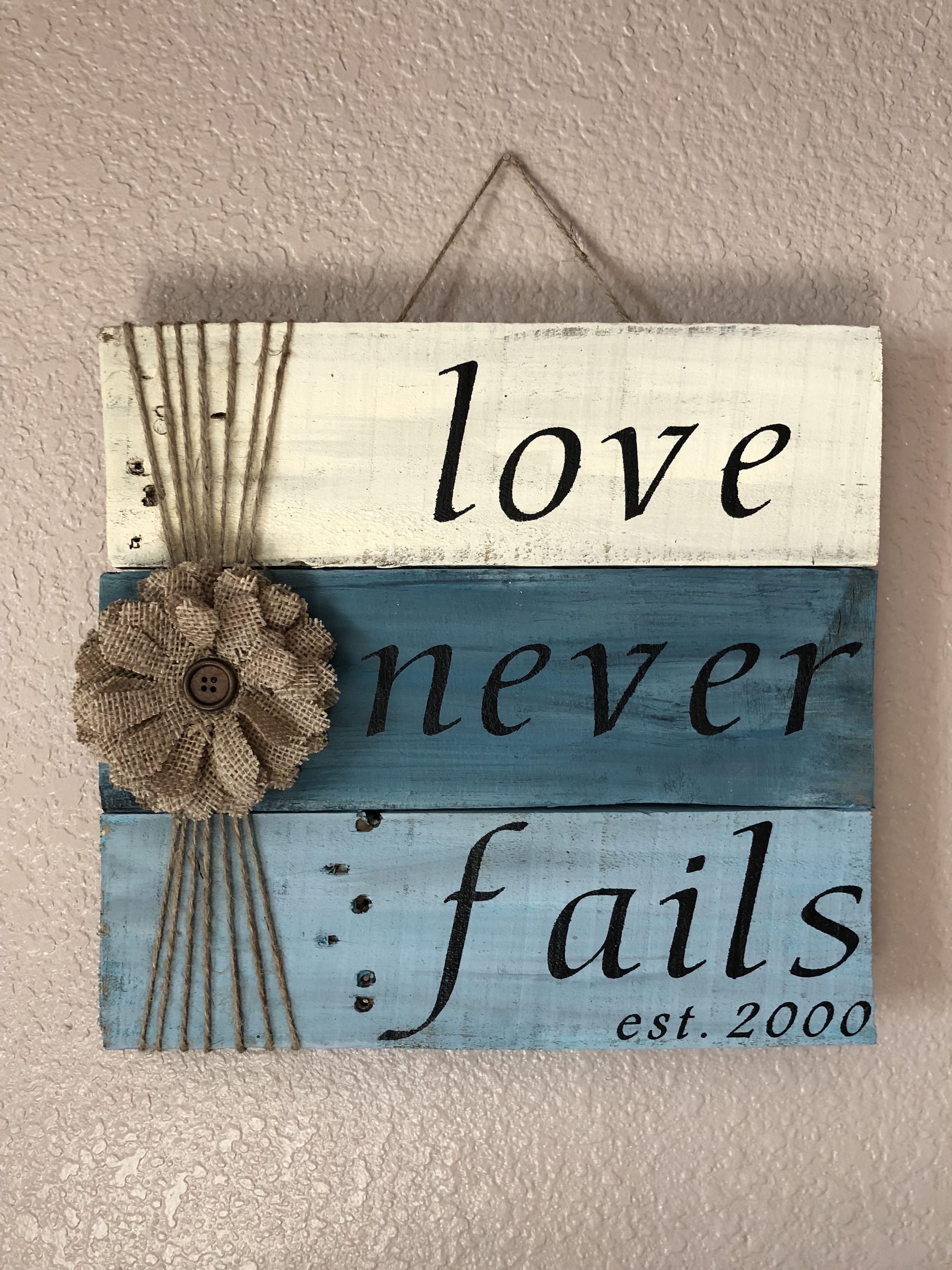 """Love Never Fails"" wooden sign"