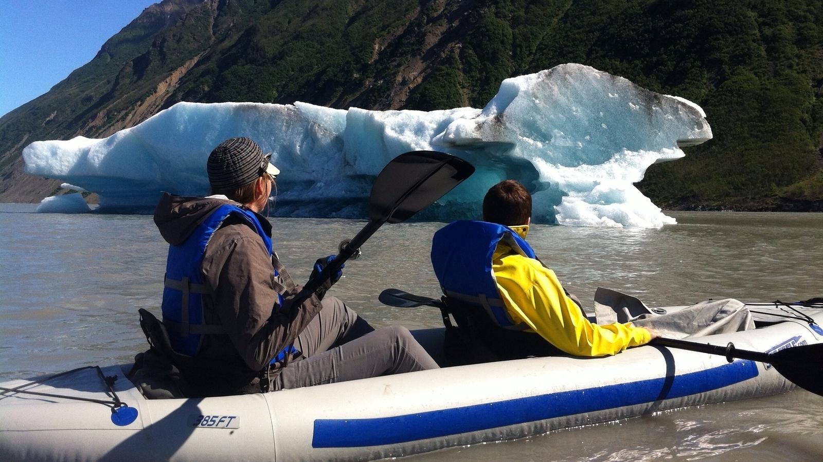 Kayakers paddling past floating glaciers
