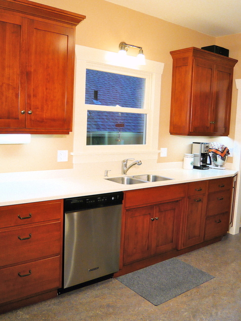 The White Corian Counter And The Warm Stained Birch Cabinets Gave The  Owners What They Wanted.