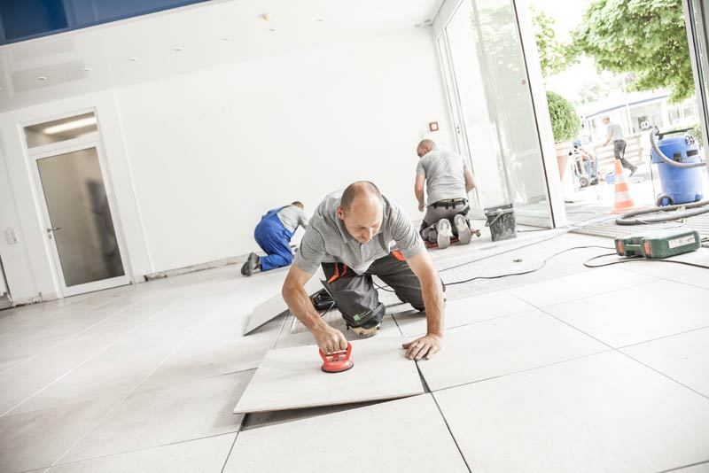 man laying drytile. No need for wet adhesives, the dry tiling installation is a fast and easy way to tile.