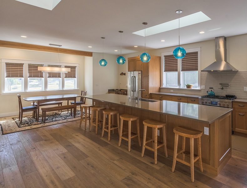 spacious kitchen design with cabinets around fridge, large fan installed above stove