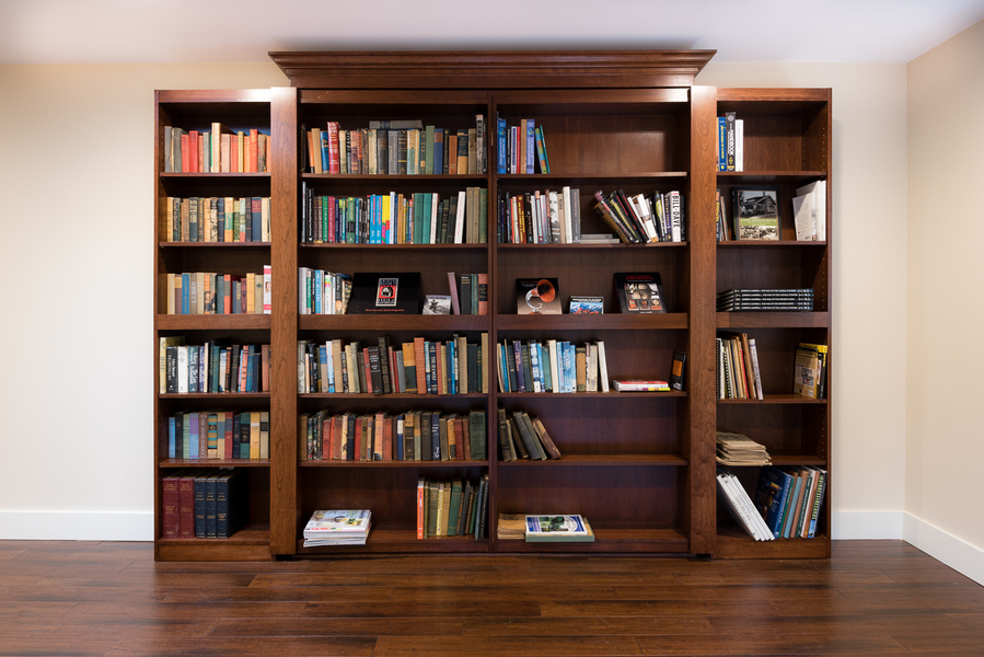 ranch house remodel by Bellingham home builders, bookshelf as hidden door to secret room, dark wood floors