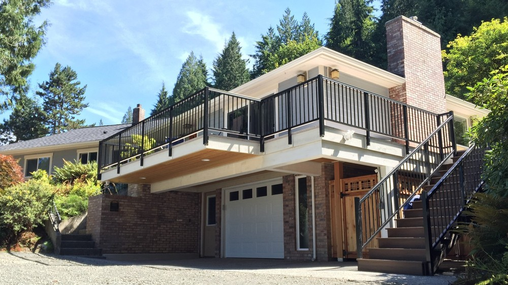 exterior of ranch house remodel by Bellingham home builders with modern stair railing and deck expansion