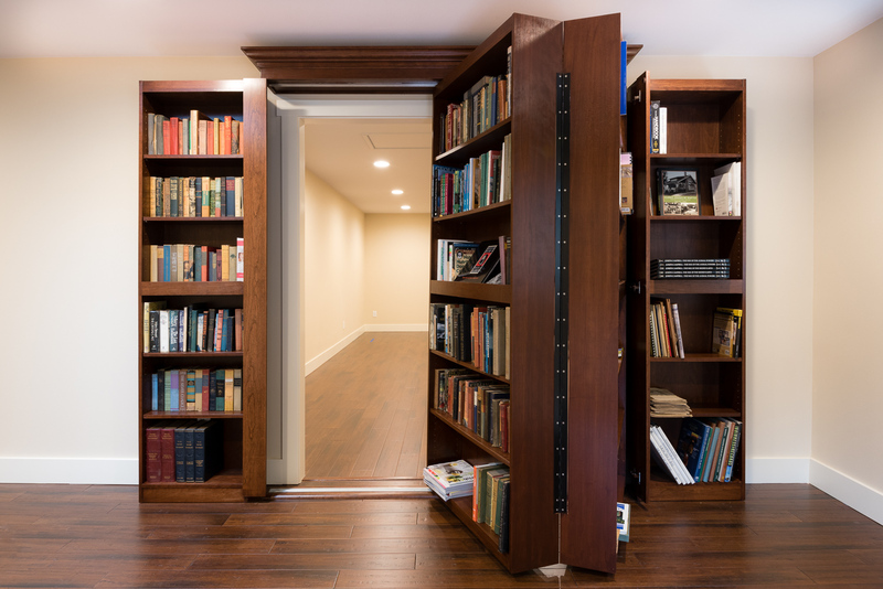 ranch house remodel by Bellingham home builders, bookshelf as hidden door to secret room, shown swung open