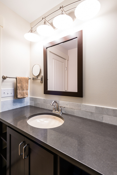 ranch house remodel by Bellingham home builders, bathroom remodel with sink, vanity mirror with lights, dark cabinets