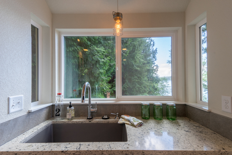 kitchen remodel of beach house by Bellingham home builders with custom sink, pendant light, peekaboo lake view