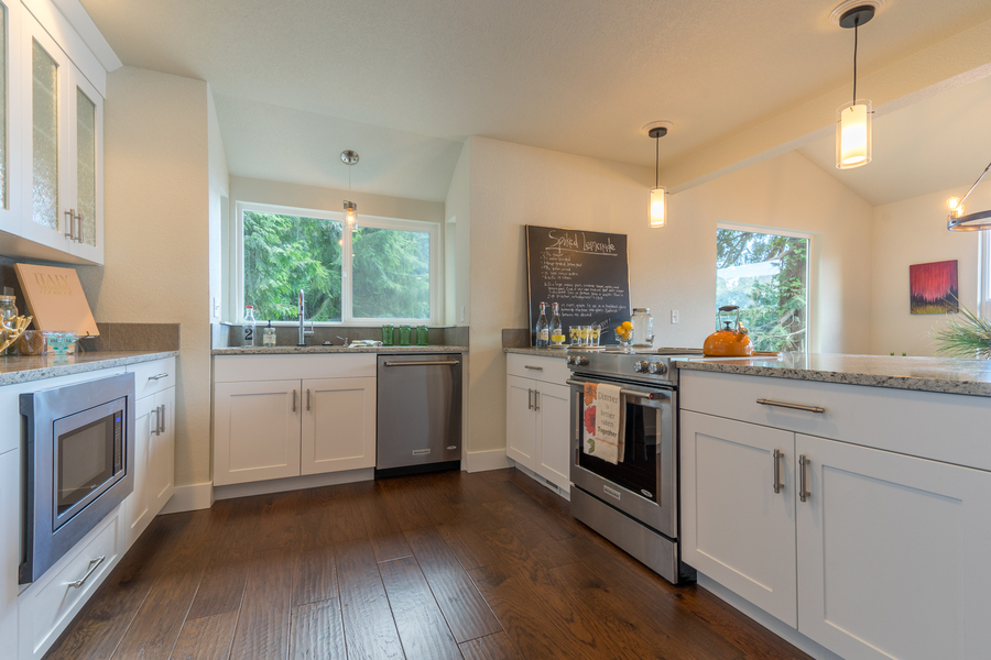 kitchen remodel of beach house by Bellingham home builders with pendant lights, glass cabinets, built in microwave, glass top stove and wood floor