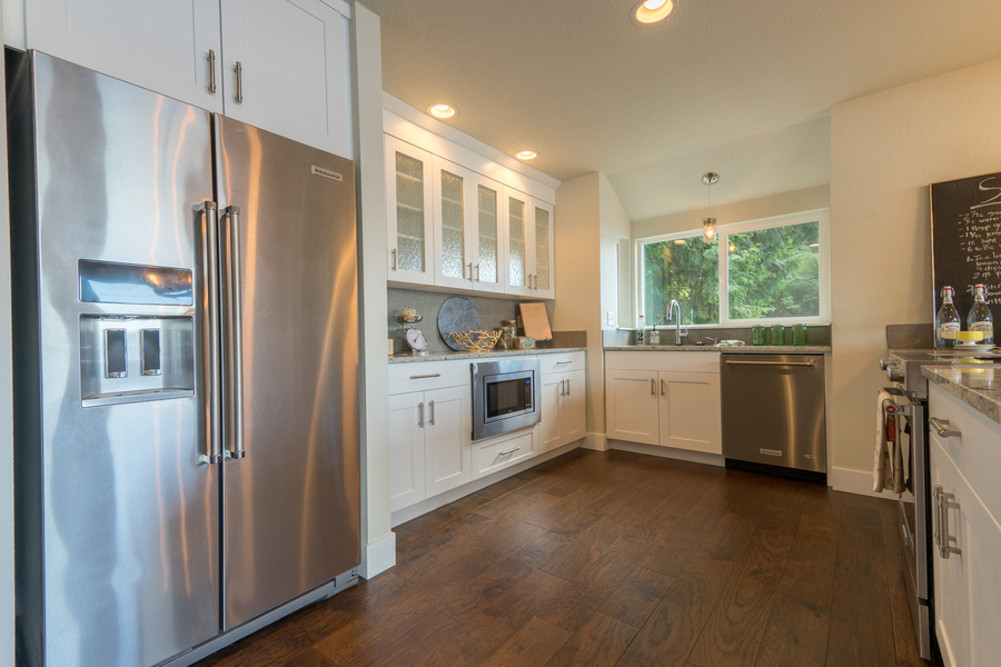 kitchen remodel of beach house by Bellingham home builders with pendant lights, glass cabinets, built in microwave, stainless steel refrigerator, wood floors