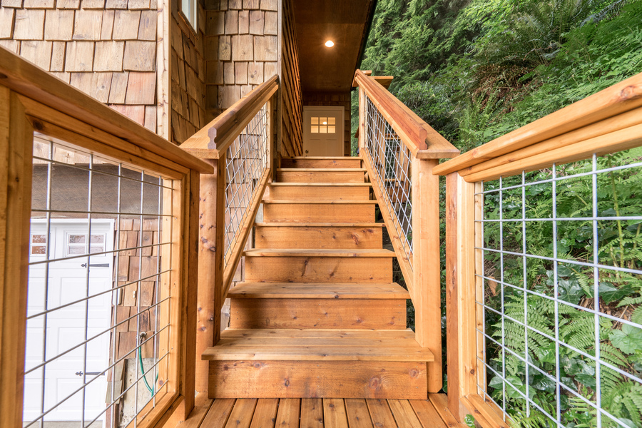 exterior staircase of beach house remodel by Bellingham home builders with modern wire railings