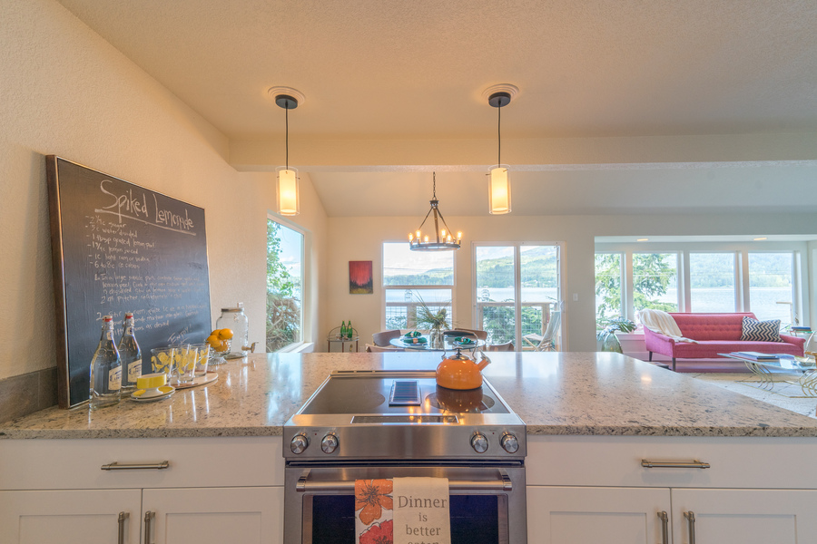 kitchen remodel of beach house by Bellingham home builders, kitchen counter with pendant lights, custom cabinets, glass top stove and lake view