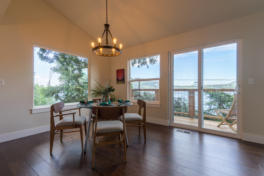 dining room in custom beach house by Bellingham home builders with large windows, glass doors and lake view