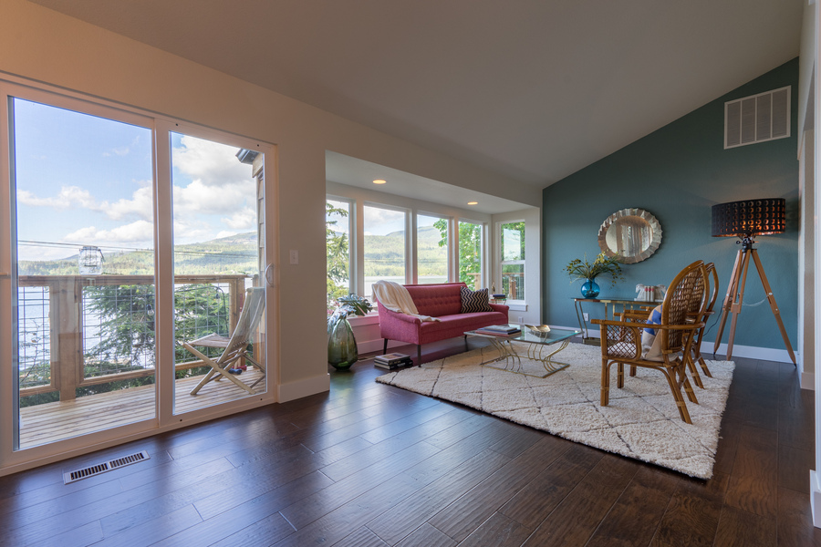 living room of beach house remodel by Bellingham home builders with view of deck and lake