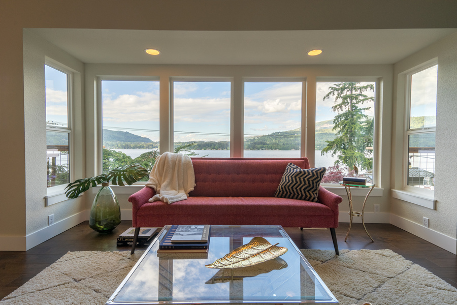 living room of beach house remodel by Bellingham home builders looking out at lake view