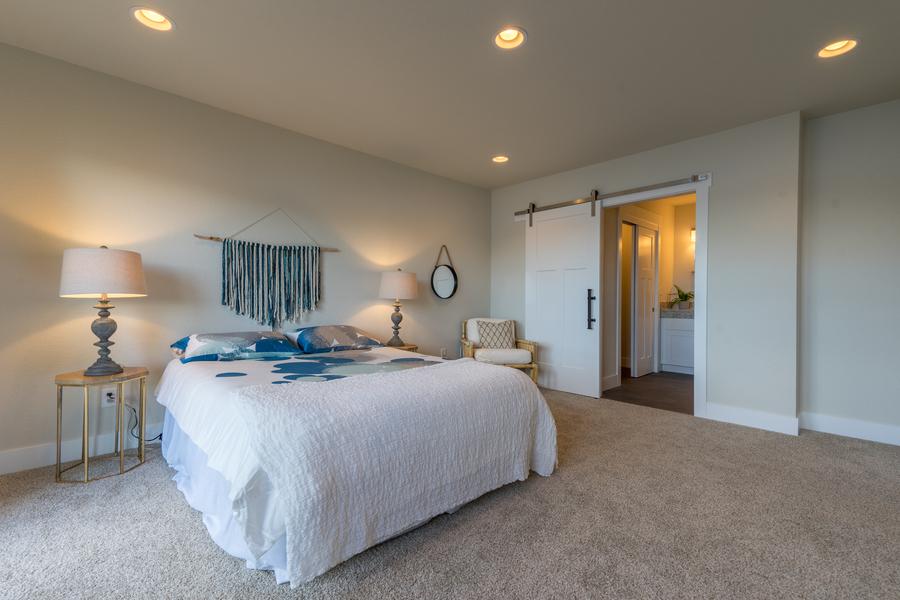 bedroom of beach house remodel with recessed lighting and barn door