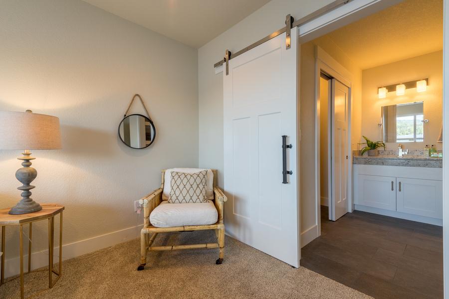 bathroom and bedroom corner of beach house remodel, barn door, view of pocket doors and vanity mirror with lights