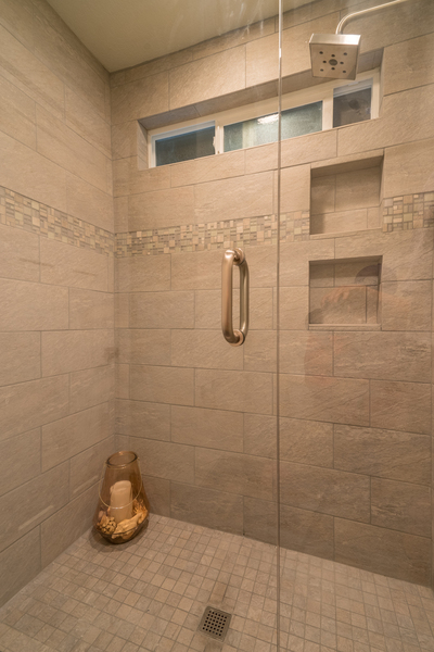 tiled shower of beach house remodel with glass door and inset shelves by Bellingham home builders