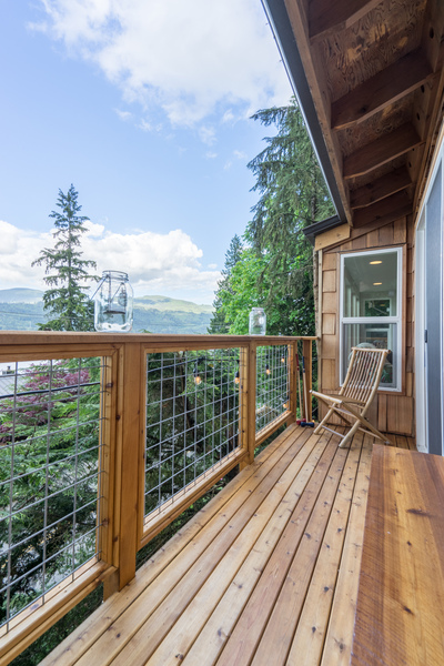 deck remodel of beach house by Bellingham home builders with modern railings and lake view