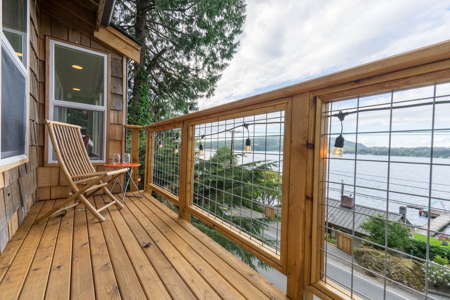 deck remodel of beach house by Bellingham home builders with modern railings, expanded seating and lake view