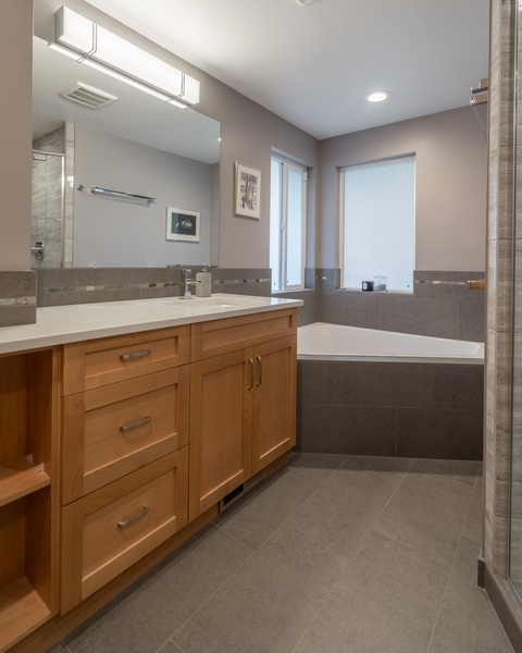 bathroom remodel by Bellingham home builders with modern cabinets, vanity with lights, travertine tile, modern fixtures