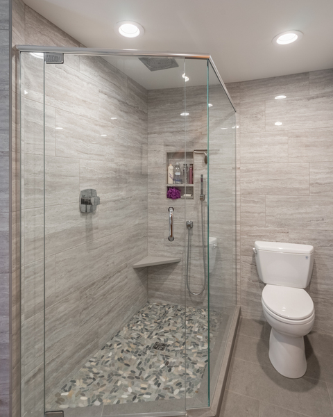 bathroom remodel by Bellingham home builders with recessed lights, glass shower doors, travertine tile, modern fixtures