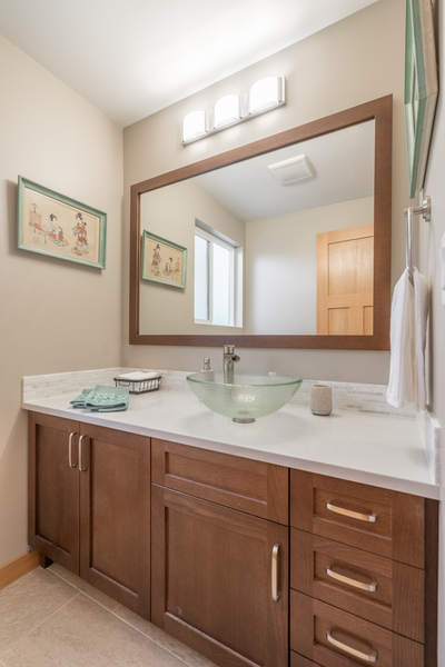 bathroom remodel by Bellingham home builders with vessel sink, dark cabinets, vanity with lights, modern fixtures