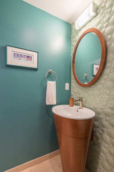 small bathroom with fun bubble texture wall, round vanity mirror, space preserving design
