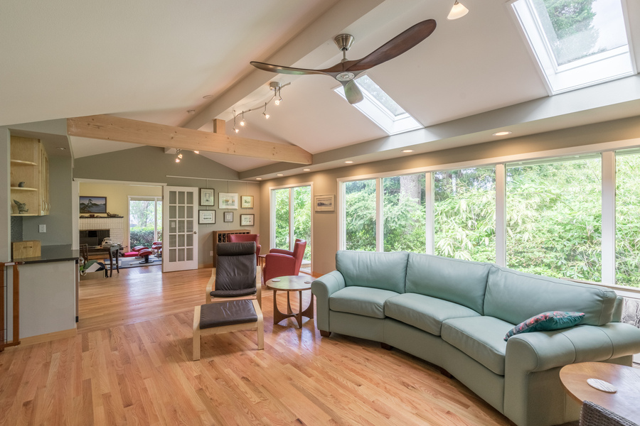 living area remodel by Bellingham home builders with skylights, large windows, natural wood floors and accents, recessed lighting