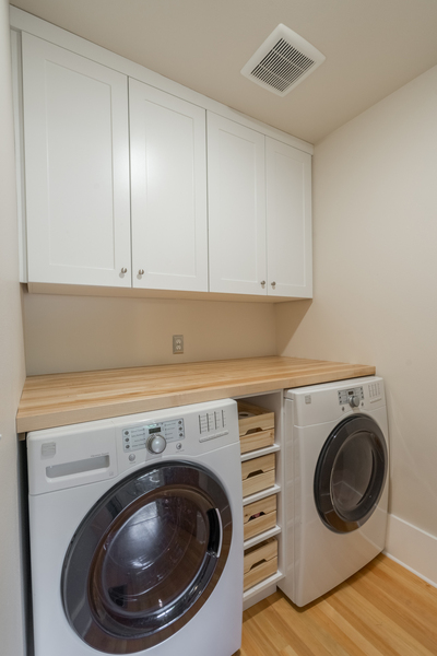 laundry room upgrade with front load washer and dryer, wood floors, white cabinets, open shelves