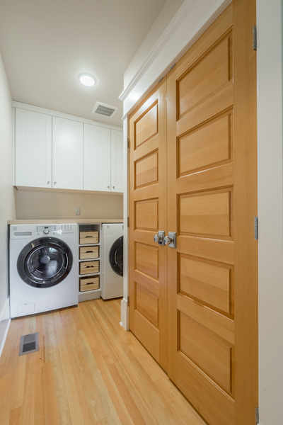 laundry room upgrade with front load washer and dryer, wood floors, light wood double doors, white cabinets