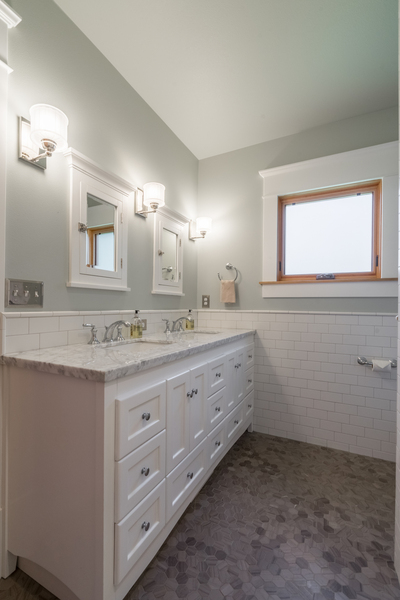 upgraded modern bathroom with double vanity, white subway tile, updated finishes