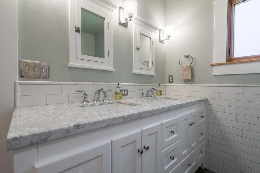 upgraded modern bathroom with double vanity, white subway tile, white cabinets, updated finishes