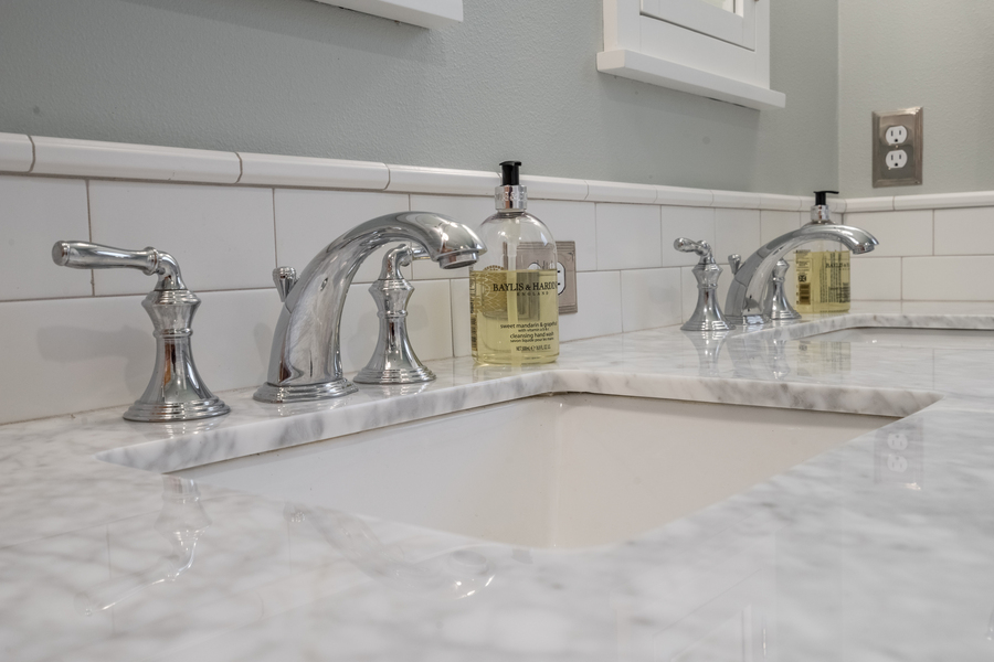 upgraded modern bathroom with double vanity, chrome faucets, updated finishes